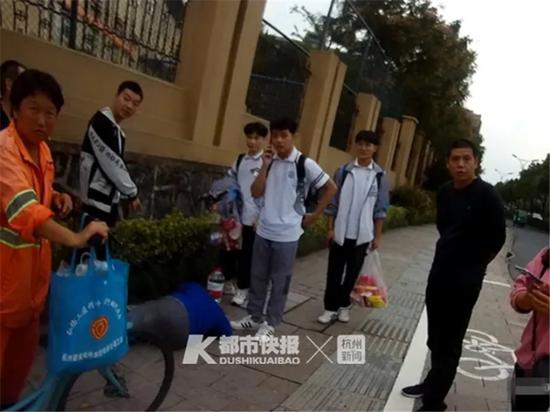 三个穿校服的男生山见杭州大伯路边晕倒围了上去